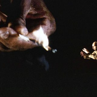 Projection of a hand holds out a lit match towards a male dancer.