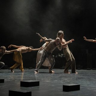 Ensemble of dancers performing onstage in Outwitting The Devil