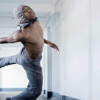 A solo male dancer spirals in mid air