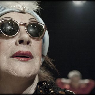 A glamorous older person wearing a pale blue silk turban studded with pearls