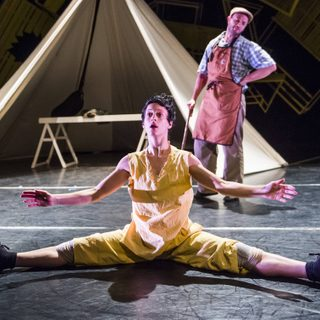 Dancer playing Pinocchio sits on the floor