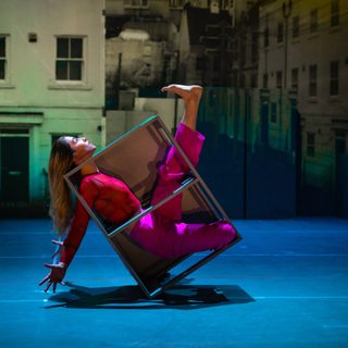 A solo dancer in a metal box-shaped frame