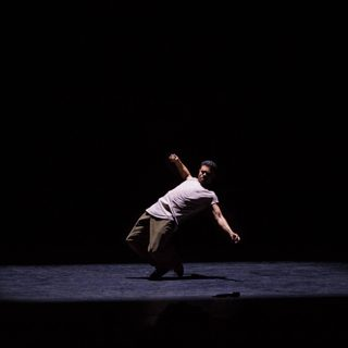 A solo male dancer performing hip hop onstage