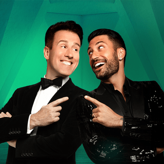 Two men mirror each other – Anton du Beke and Giovanni Pernice, each pointing one finger at the other with a laughing smile.