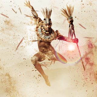 A dancer leaps towards us in mid-air, against a sandy background spattered with red and brown pigment.