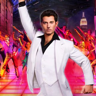 A disco dance floor full of dancers, front and centre a man dressed in a white tux posing with his arm pointed up